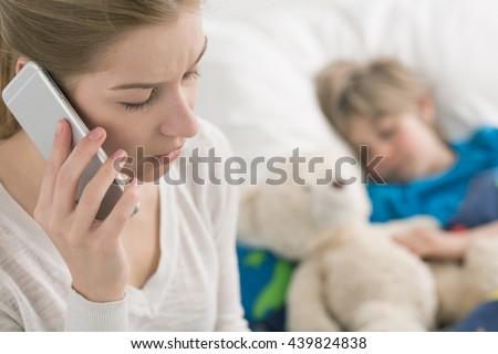 Shot of a concerned young mother talking on the phone and her sick son sleeping on a bed
