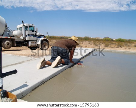 Shot of a construction worker smoothing out a freshly poured concrete slab using a hand trowel. Horizontally framed shot.