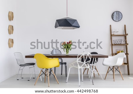 Shot of a creative dining room with a big table and six different chairs