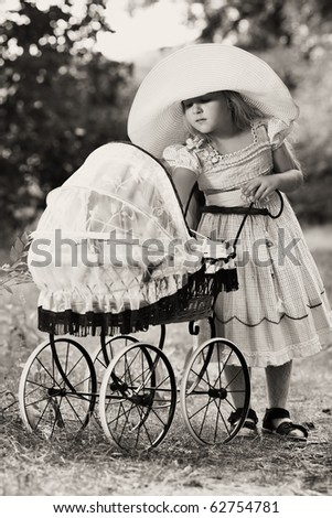 Shot of a cute girl walking with baby buggy at summer park. - stock photo