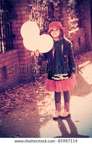 Shot of a cute girl walking with balloons at the park.