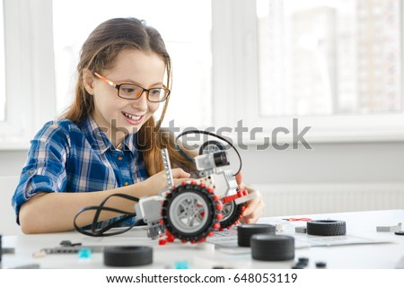Shot of a cute young girl smiling joyfully building a robot copyspace constructor engineering playing childhood kids hobby leisure lifestyle people toys robotics technology intelligence learning