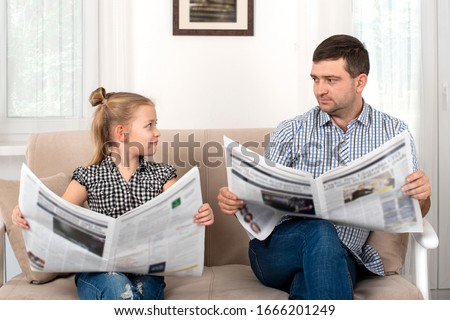 Shot of a daughter and dad spending time together at home. They sit on the sofa and read the newspapers together same way.  Daughter imitates her father. Photo stock ©