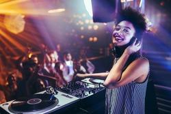 Shot of a female DJ playing music at a nightcub