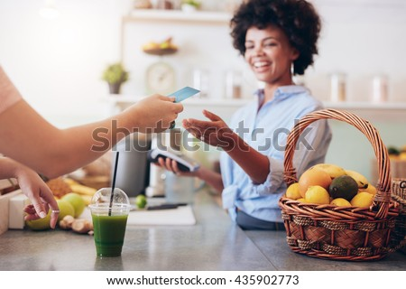 Shot of a female juice bar owner taking payment from customer. Female customer paying for juice with credit card.