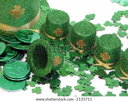 Shot of a few green top hats with a shamrock confetti and metallic green coins.  Over white.
