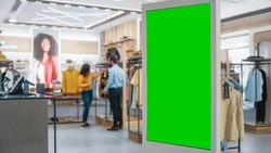Shot of a Floor-Standing LCD Touch Screen Display with Green Screen Chroma Key Mock Up Standing in Clothing Store. Diverse People in Fashionable Shop, Choosing and Buying Stylish Clothes.