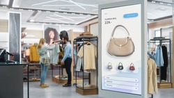 Shot of a Floor-Standing LCD Touch Screen Display with User Interface of Online Clothing Shop Standing in Clothing Store. Self service Checkout with Hand Bag. Diverse People in Shop Buying Clothes.