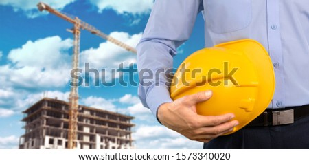 Shot of a foreman holding a hardhat on the construction background