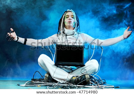 Shot of a futuristic young man sitting with a laptop and wires.