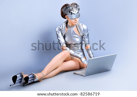 Shot of a futuristic young woman with a laptop. - stock photo