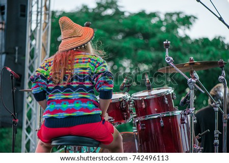 Shot of a girl with colorful clothes and orange hat playing drums on stage during music festival in summer. Band performing their songs. #742496113