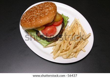 Shot of a grilled hamburger with fries and all the fixins.\\ Very high resolution. You can see cracks in the bun.