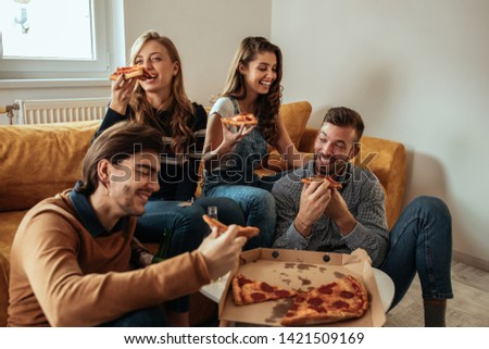 Shot of a group of friends enjoying pizza together