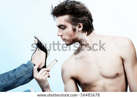 Shot of a handsome man holding woman's leg in elegant shoes. - stock