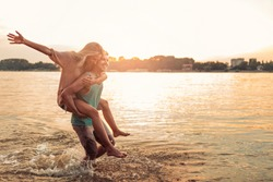 Shot of a handsome young man giving his girlfriend a piggyback ride on the beach