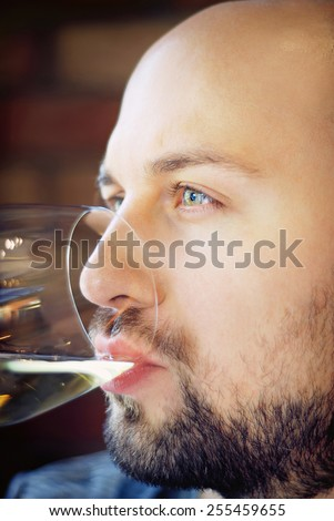 Shot of a handsome young man with beard and green eyes drinking wine in restaurant/Attractive man in restaurant