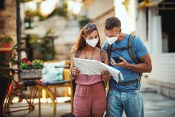 Shot of a happy couple with protective N95 mask spending time on vacation and exploring a Mediterranean city at corona pandemic.