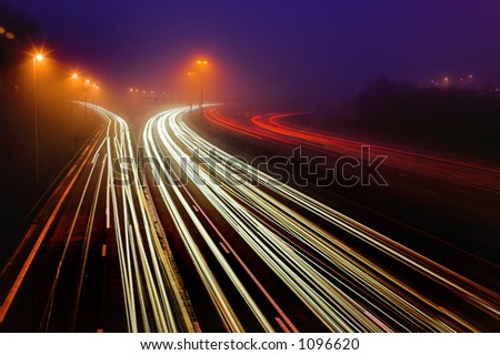 Shot of a highway in the mist, with traffic trails and a blue background