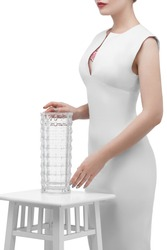 Shot of a lady's lower face's part with floral tattoo on her chest, posing in white dress on solid color background. The woman with red lipstick is touching a waterglass, which stands on high chair.