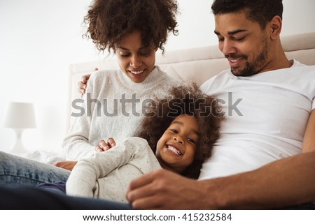 Shot of a laughing little girl lying in bed with her parents in the morning.