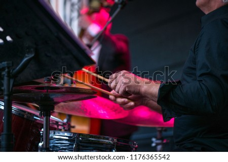 Shot of a man playing drums on stage during music festival in summer. Band performing their jazz songs. Live concert of electronic music at night. Male musicians playing saxophone, drums, cello  #1176365542