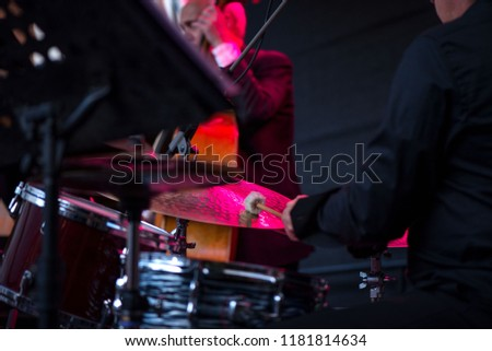 Shot of a man playing drums on stage during music festival in summer. Band performing their jazz songs. Live concert of electronic music at night. Male musicians playing saxophone, drums, cello  #1181814634