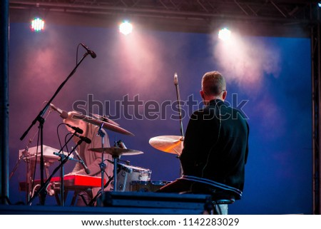 Shot of a man playing drums on stage during music festival in summer. Band performing their songs. Live concert of electronic music at night. Colorful lights and lasers #1142283029