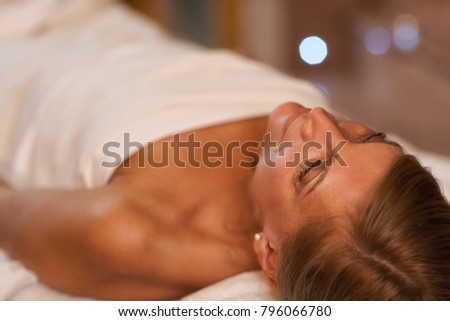 Shot of a mature blond haired woman relaxing at the spa salon lying on massage table with her eyes closed smiling joyfully copyspace happiness serenity relaxation treatment pampering therapy #796066780