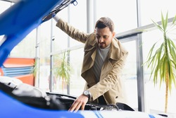 Shot of a mature man examining engine of a new automobile at the car dealership looking under the hood copyspace mechanics modern technology driving vehicle horsepower motor automotive.