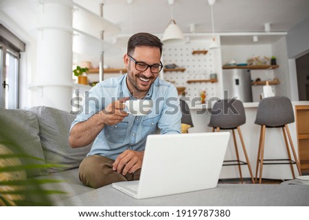 Shot of a mature man sitting on a chair in his living room using a laptop. Man with good vibes sitting on the sofa. Man studying and working on laptop at home