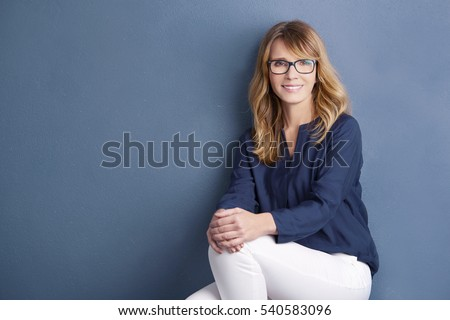 Shot of a mature woman with pretty face sitting by the wall while wearing casual clothing and smiling to the camera. #540583096