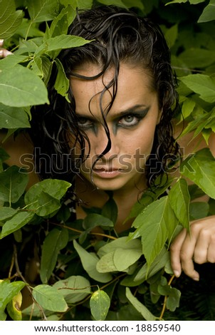 Shot of a model's face with heavy eye makeup surrounded by green leaves
