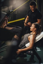 Shot of a muscular young woman in sportswear working out with personal trainer at the gym. She is doing exercises for her legs on leg press machine.