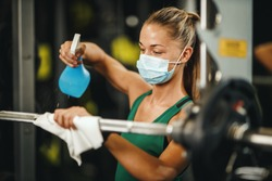 Shot of a muscular young woman with protective mask cleaning fitness gym equipment before workout during Covid-19 pandemic.