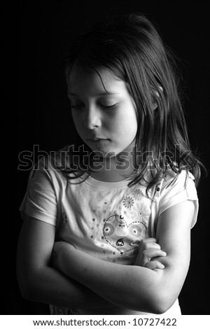 Shot of a pretty seven year old girl looking down with her arms crossed, against a black background II