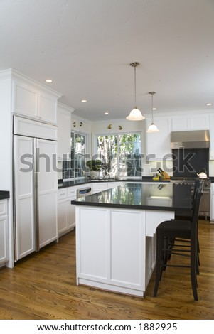 Shot of a remodeled kitchen featuring white custom cabinets and stainless steel appliances.