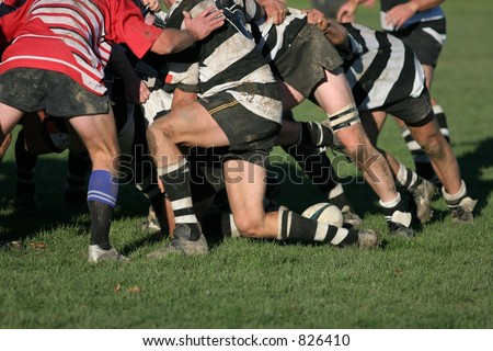 Shot of a rugby scrum at ground level with the ball coming back.  Logos on boots etc. removed.