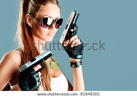 Shot of a sexy military woman posing with guns. - stock photo