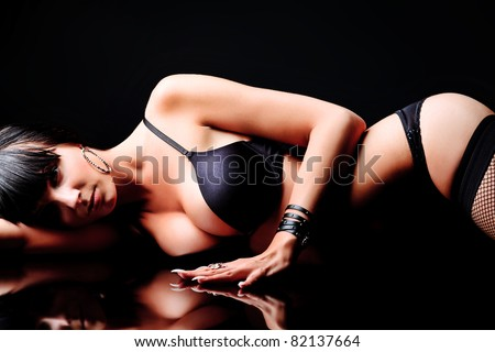 Shot of a sexy woman in black lingerie over black background.