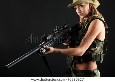 Shot of a sexy woman soldier posing against black background.