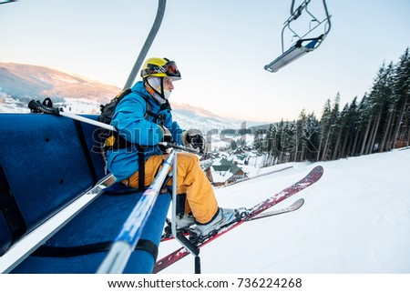 Shot of a skier sitting on a ski lift chair riding up to the top of the mountain copyspace winter extreme sports concept #736224268