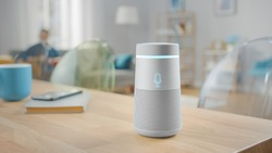 Shot of a Smart Speaker with Artificial Intelligence Assistant Standing on the Table in Bright Cozy Living Room.