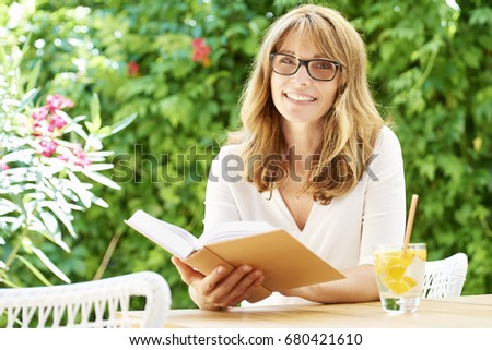 Shot of a smiling attractive middle aged woman relaxing outdoor while reading a book.  #680421610