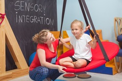 Shot of a smiling girl enjoying a sensory therapy on a swing while her physiotherapist assisting her