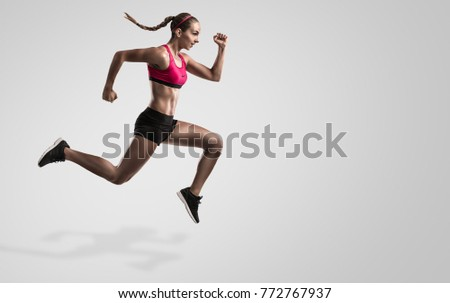 Shot of a sporty young woman runing and jumping against a gray background