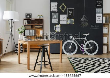 Shot of a stylish studio interior with a minimalistic workspace and a big blackboard