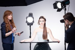 Shot of a stylist, a model and a photographer during a professional photoshoot
