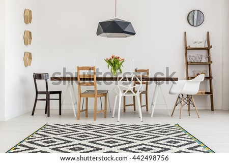 Shot of a table and different chairs in a dining room