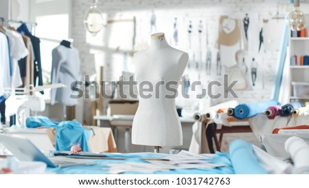 Shot of a Tailoring Mannequin that Stands in a Bright and Sunny Studio. Various Sewing Items and Colorful Fabrics Laying around, Mannequins Standing, and Sketches Pinned to the Wall.